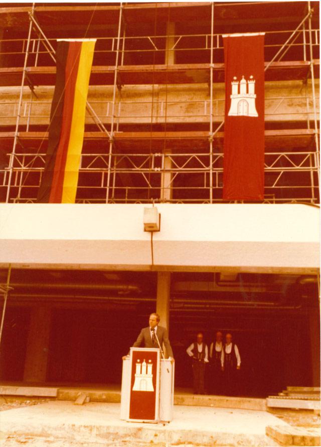 Bau-Senator Volker Lange am Rednerpult (im Hintergrund 3 Handwerker)